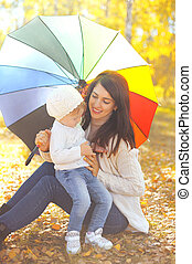 Happy smiling mom and child with umbrella together in autumn park