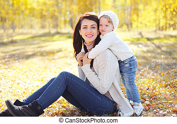 Happy smiling mom with little child in sunny autumn park