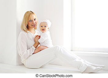 Happy smiling mother and baby at home in white room near window