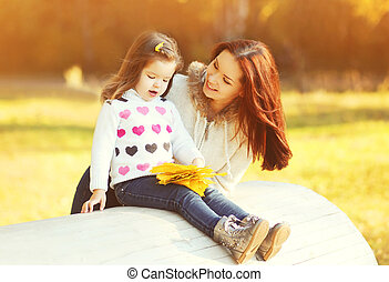 Happy smiling mother and child having fun in sunny autumn day
