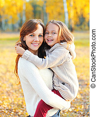 Happy smiling mother and child having fun together in autumn day