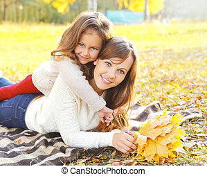 Happy smiling mother and child having fun together with yellow maple leafs in autumn day lying on plaid
