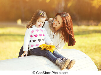Happy smiling mother and child in sunny autumn day