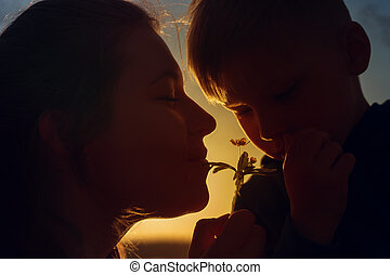 Happy smiling mother and child smelling flower