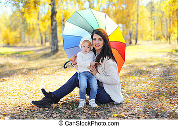 Happy smiling mother and child with umbrella together in autumn park