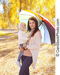Happy smiling mother and child with umbrella walking in autumn park