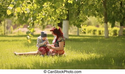 Happy smiling mother and son child sitting on grass and play in summer day