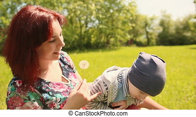 Happy smiling mother and son child sitting on grass and play with dandelion outdoor