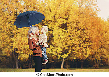 Happy smiling mother holding child with umbrella having fun together over autumn trees background