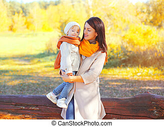 Happy smiling mother holding on hands child in autumn day