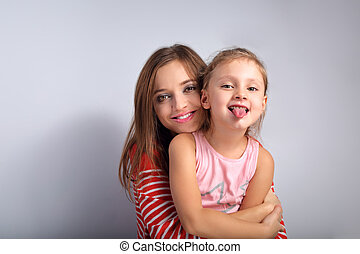 Happy smiling mother hugging with love her frolic grimacing kid showing the tongue on blue background