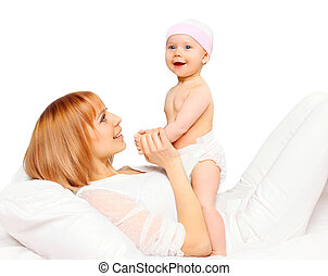 Happy smiling mother playing with baby lying on bed
