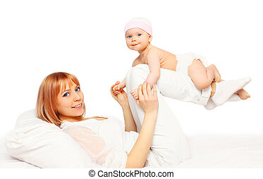 Happy smiling mother playing with baby on bed