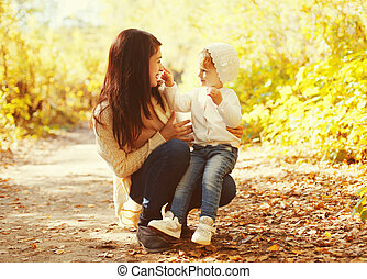 Happy smiling mother playing with child in warm autumn day