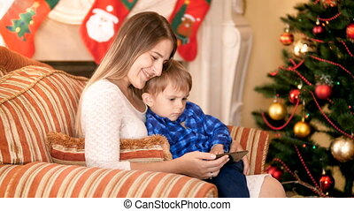 Happy smiling mother sitting in armchair with her little son...
