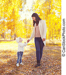 Happy smiling mother walking with child in warm sunny autumn day