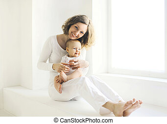 Happy smiling mother with baby at home in white room near window