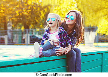 Happy smiling mother with child daughter having fun together in the park