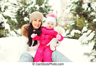 Happy smiling mother with child on snow in winter day