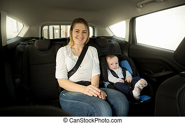 Happy smiling mother with her baby on back seat
