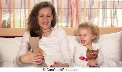 happy smiling mother with her child girl playing with toy cats on bed