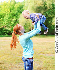 Happy smiling mother with son child having fun outdoors in park
