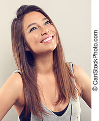 Happy smiling natural makeup latina woman posing with long hairstyle and looking up on grey background. Closeup toned portrait