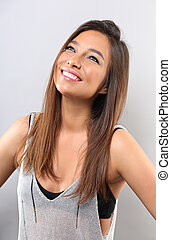 Happy smiling natural makeup latina woman posing with long hairstyle and looking up on grey background. Closeup portrait