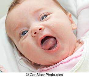Happy smiling newborn with blue eyes.