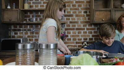 Happy Smiling Parents Looking At Children Cutting Vegetables Together In Kitchen Family Cooking Food At Home
