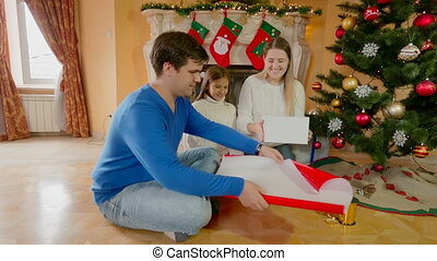 Happy smiling parents with daughter wrapping present for Christmas
