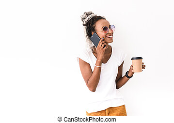 Happy smiling positive young african woman with dreads posing isolated over white wall background talking by mobile phone drinking coffee.