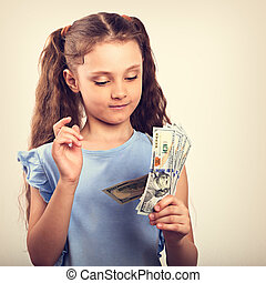 Happy smiling rich kid girl holding and count money. Vintage toned portrait