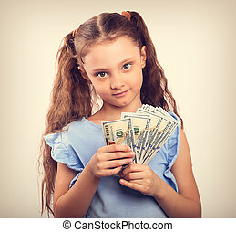 Happy smiling rich kid girl holding money two hands. Vintage toned portrait