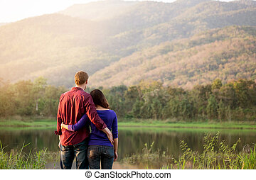 Happy Smiling Romantic couple relaxing in love at the autumn beautiful park the sunset, valentine concept