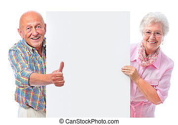 happy smiling senior couple with a blank board