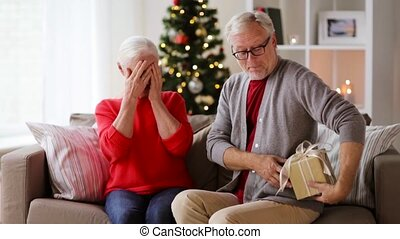 happy smiling senior couple with christmas gift