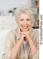Close up portrait of a happy smiling senior woman resting her chin on her hands and looking directly at the camera