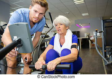 happy smiling senior woman exercising in a gym