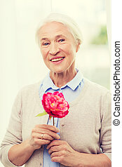 happy smiling senior woman with flower at home