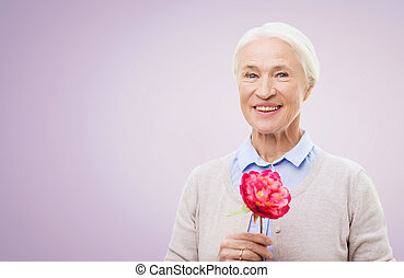 happy smiling senior woman with flower