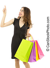 Happy smiling shopping woman pointing up to copy space