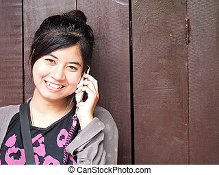 happy smiling teenage girl with the mobile phone