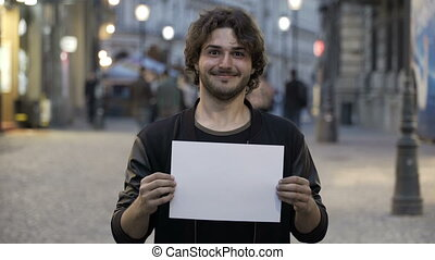 Happy smiling teenage man holding a blank copy space banner on the street in the city
