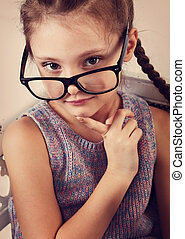 Happy smiling thinking kid girl in eyeglasses looking and thinking about. Closeup vintage studio toned portrait