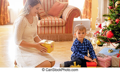 Happy smiling toddler boy sitting under Christmas tree with mother and holding gifts in boxes