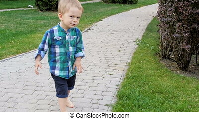 Happy smiling toddler boy walking on pathway at park