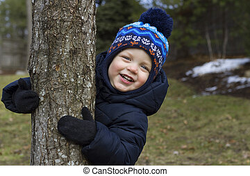 Happy smiling toddler hugs tree in a park. Copy space