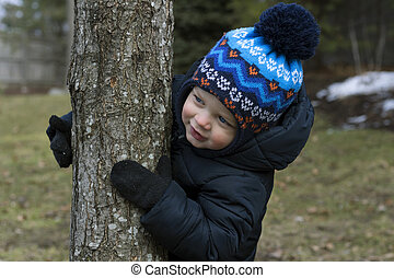 Happy smiling toddler hugs tree in a park.