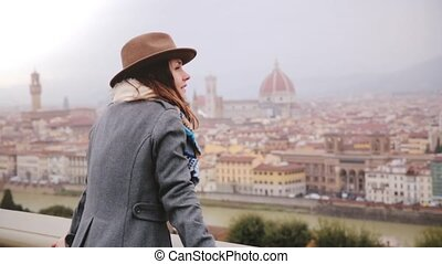 Happy smiling tourist girl in warm clothes walks up to enjoy beautiful panoramic view of Florence, Italy on a rainy day.